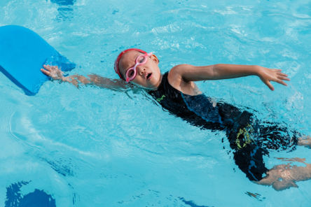child swimming front crawl with float